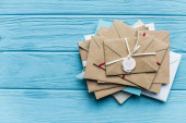 top view of wooden blue background with envelopes and heart