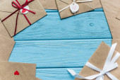 top view of wooden blue background with envelopes and hearts