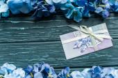 vrchní pohled na dřevěné zelené pozadí s modrými květinovými okraji a obálkou