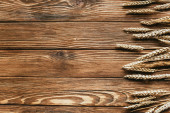 top view of wheat ears border on wooden background