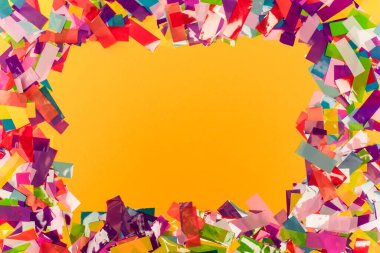 Top view of colorful bright confetti frame on orange background stock vector