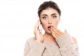 sokkos nő eltakarja száját kézzel, miközben beszél okostelefon elszigetelt fehér