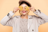 joyful woman in stylish trench coat and beret covering eyes with yellow leaves isolated on peach