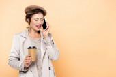 trendige Frau im Herbst-Outfit, die mit dem Handy telefoniert, während sie Coffee to go auf Pfirsich hält