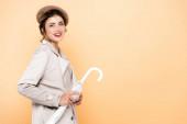 radostná žena ve stylovém podzimním oblečení drží složený deštník při pohledu na fotoaparát na broskev