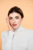 young woman in turtleneck touching face while posing isolated on peach