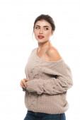 stylová žena v prolamovaném svetru při pohledu pryč, zatímco pózuje izolované na bílém