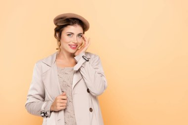 Young woman in stylish autumn outfit touching face while looking at camera on peach stock vector