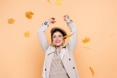 Excited woman in trench coat and beret throwing yellow leaves on peach stock vector