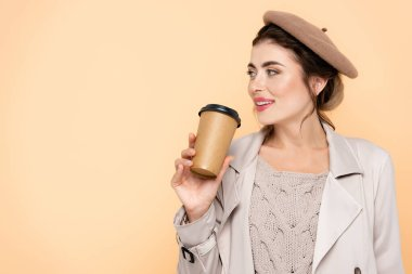 Fashionable woman in autumn outfit holding coffee to go while looking away isolated on peach stock vector