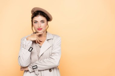 Fashionable woman in trench coat and beret touching chin while looking at camera on peach stock vector