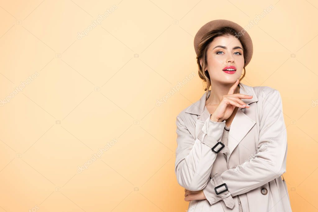 Sensual woman in stylish trench coat and beret looking at camera on peach stock vector