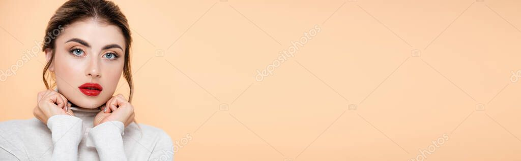 Horizontal crop of stylish woman holding hands near face while looking at camera isolated on peach stock vector