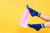 Oříznutý pohled na růžový papírový sáček visící na noze ženy v ponožkách izolovaných na žlutém pozadí