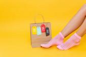 Oříznutý pohled na ženské nohy v ponožkách s růžovými pruhy v blízkosti papírové tašky s visačkami s prodejem slova izolované na žluté