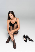 Fotografie Sexy junge erwachsene Frau mit überkreuzten Beinen, schaut in die Kamera, während sie neben schwarzen Schuhen auf grau sitzt