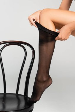 Cropped view of woman putting stocking on, while leaning on black chair on grey