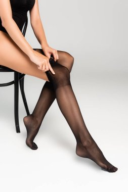 Cropped view of woman putting black stocking on while sitting on chair