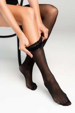 Partial view of woman putting black stocking on while sitting on chair