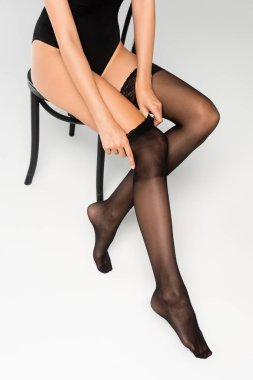 Cropped view of woman in bodysuit putting black stocking on while sitting on chair