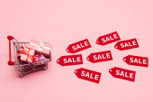 Photo top view of toy shopping cart with presents near tags with sale lettering on pink, black friday concept
