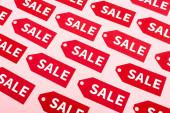 Draufsicht auf Etiketten mit Sale-Schriftzug auf rosa, Black Friday-Konzept