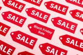 Photo top view of red labels with sale and black friday lettering on pink