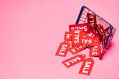 prodejní štítky v blízkosti nákupního košíku na růžové, černé pátek koncept