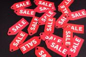 Draufsicht auf rote Etiketten mit Verkaufsbuchstaben auf schwarzem Hintergrund