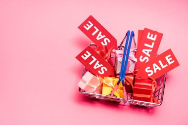 Top view of shopping basket with presents and sale tags on pink stock vector