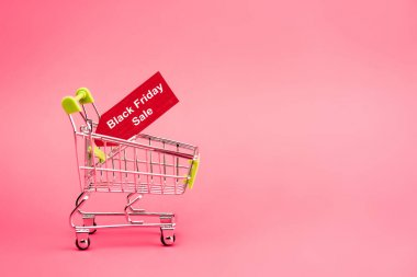 Red tag with black friday sale lettering in shopping cart on pink stock vector