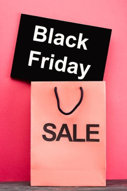 Placard with black friday lettering near shopping bag on pink stock vector