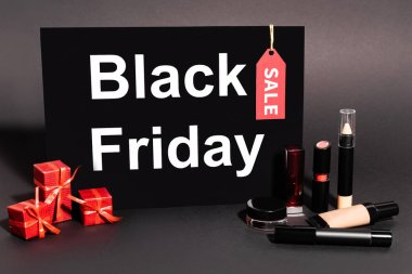 Placard with black friday lettering and gifts near decorative cosmetics on dark background stock vector