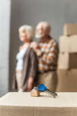 blurred view of senior couple moving into new house and keys on foreground, moving concept