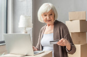 senior žena dělat on-line nákup s kreditní kartou a notebookem