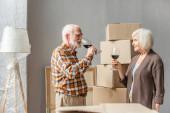 Glückliches Seniorenpaar feiert Einzug in neues Haus mit Glas Wein