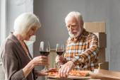 starší pár držící sklenice vína a muž brát kus pizzy v novém domě