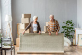 senior couple rolling carpet and looking at each other with boxes, frames and plant on background