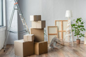 cardboard boxes, frames, ladder, lamp and plant in empty room, moving concept