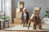 Photo senior couple rolling carpet on knees with boxes, frames on background