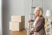 usměvavá starší žena sedící na žebříku a dívající se stranou s kartónovými krabicemi na pozadí, pohybující se koncept