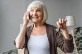 glückliche Seniorin telefoniert und hält Schlüssel in neuem Haus, bewegliches Konzept