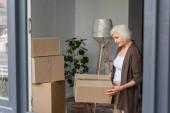 veselá starší žena držící lepenkovou krabici, pohyblivý koncept