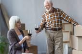 starší pár slaví stěhování do nového domu s sklenicemi vína
