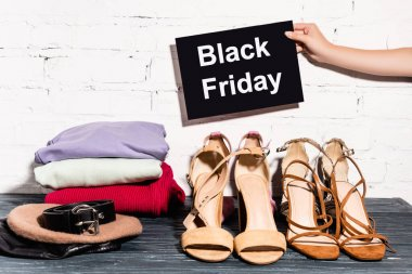 Cropped view of woman holding placard with black friday lettering near shoes, clothing, beret and belt and brick wall stock vector