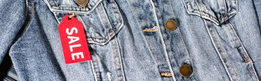 Close up of red sale tag on blue denim jacket, panoramic crop stock vector