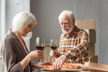Senior couple holding glasses of wine and man taking piece of pizza in new house stock vector