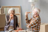 smějící se starší pár jíst pizzu v novém domě a lepenkové krabice na pozadí