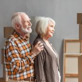 veselý manžel objímání manželka ramena v novém domě