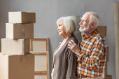 cheerful husband hugging wife shoulders in new house with cardboard boxes on background